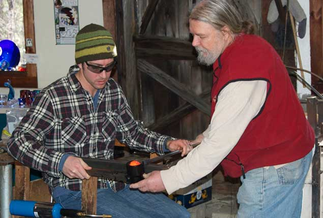 Robert Burch assists first time glass blower in making a handblown paperweight.